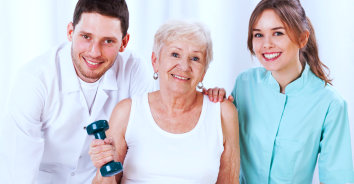 elderly woman holding a dumbbell with two caregivers