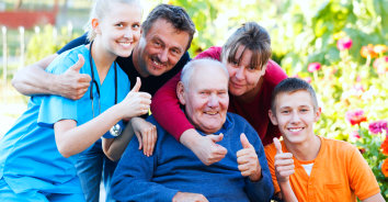 elderly man and his family with a caregiver