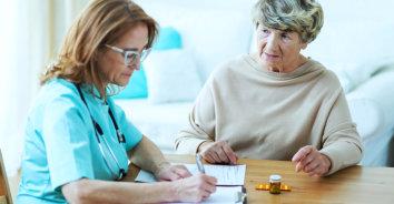 female doctor giving prescription to an elderly woman