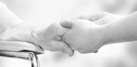 caretaker's hands holding an elderly woman's hand
