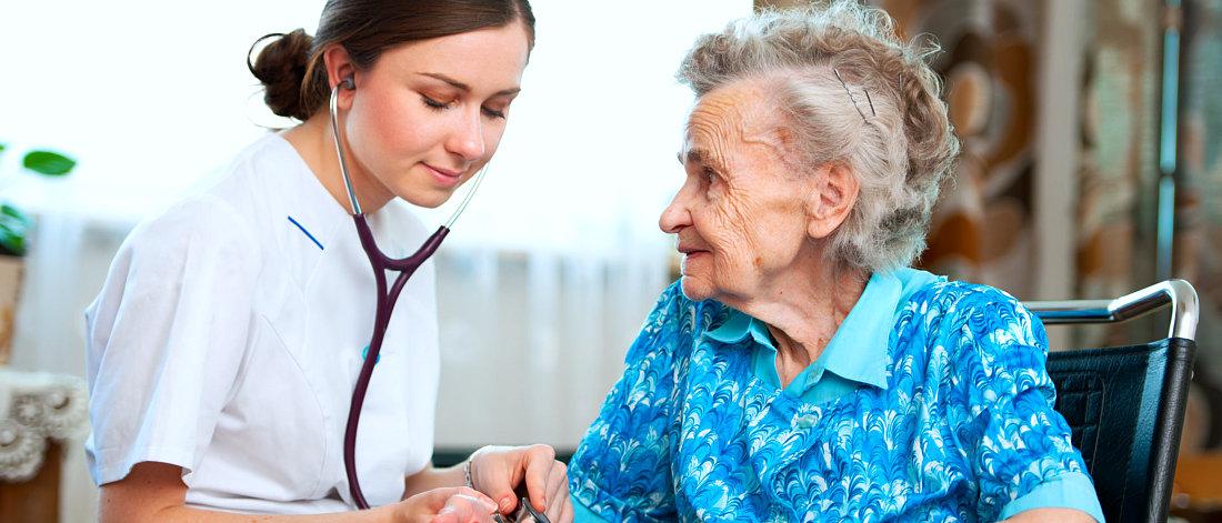 elderly woman in wheelchair having her blood pressure checked
