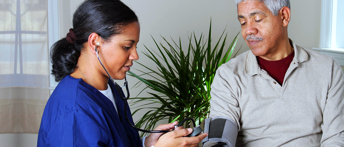 caregiver in blue checking an elderly man's blood pressure
